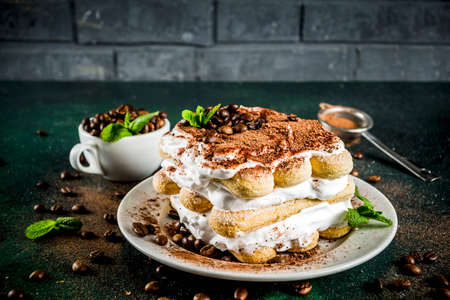Homemade italian dessert tiramisu on plate, with cocoa and coffee beans, decorated with mint, dark green background copy space 免版税图像