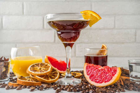 Negroni coffee cocktail with ingredients - coffee, orange, grapefruit, spices, liqueur, white marble background copy space