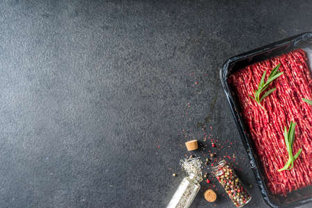 Raw minced beef meat with herbs and spices for cooking, black concrete or stone table Stock Photo