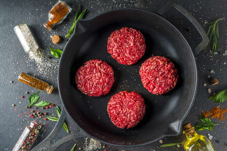 Raw minced meat beef burger cutlets. Cooking meat and burgers background with olive oil. herb, spices, black stone or concrete table, above, copy space