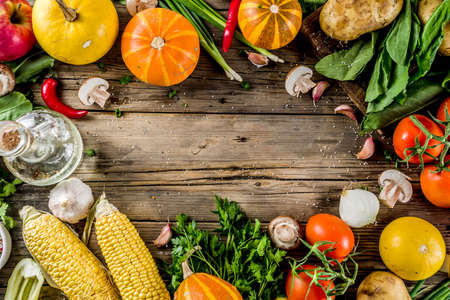 Concept de nourriture d'automne. Légumes et ingrédients biologiques sains de la récolte citrouille, légumes verts, tomates, maïs, fond de table de cuisine en bois. Ingrédients de cuisine de saison de Thanksgiving.