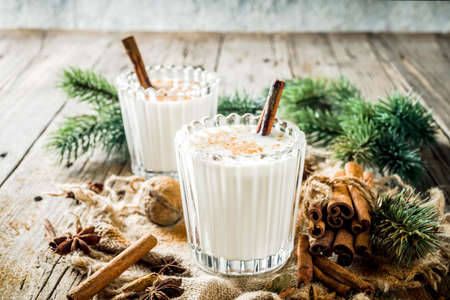 Classic Christmas drink Eggnog, chilean Cola de mono (monkey tail) cocktail, or Puerto Rican Coquito  eggnog, on old wooden background with pine tree branches copy spaces Imagens