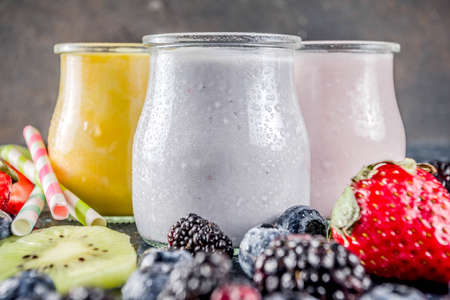 Summer fruits and berries smoothie drink. Vitamin diet snack beverage, with blueberries, strawberries, blackberries, kiwi. Dark blue concrete background copy space Stockfoto