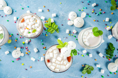 Variations of bitter and dairy hot chocolate with funny marshmallow in form snowmen, white bears, with sweets and decorative leaves, light blue background, top view copy space