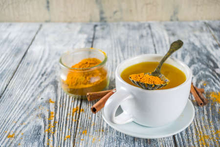 Golden Cinnamon Turmeric Tea. Trendy hot drink with turmeric and spices, Wooden background copy space