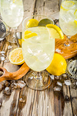Trendy summer cold drink. St Germain French Spritz cocktail with lemon slices, old rustic wooden background copy space