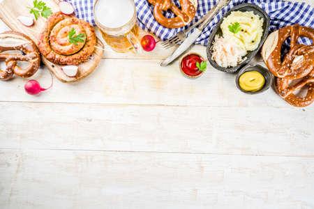 Oktoberfest food menu, bavarian sausages with pretzels, mashed potato, sauerkraut, beer bottle and mug, white wooden background copy space top view