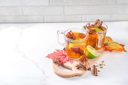 Hot spicy autumn tea with cinnamon, anise, lemon, with autumn decoration, leaves and spices