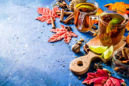 Hot spicy autumn tea with cinnamon, anise, lemon, with autumn decoration, leaves and spices Stock fotó - 127891010
