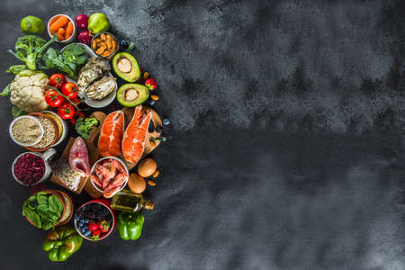 Pescetarian diet plan ingredients, healthy balanced grocery food, fresh fruit, berries, fish and shellfish clams, black stone concrete background copy space Stok Fotoğraf
