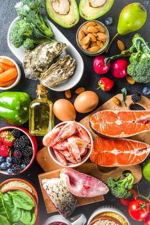 Pescetarian diet plan ingredients, healthy balanced grocery food, fresh fruit, berries, fish and shellfish clams, black stone concrete background copy space Reklamní fotografie