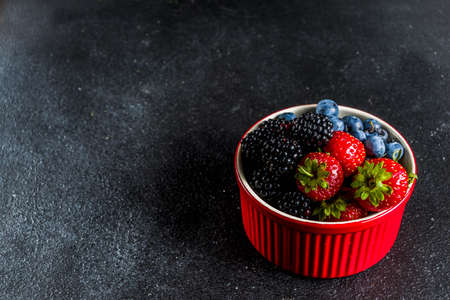 Fresh raw organic berries in a small bowl - blueberries, strawberries, blackberries. On a black concrete stone background