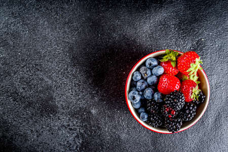 Fresh raw organic berries in a small bowl - blueberries, strawberries, blackberries.