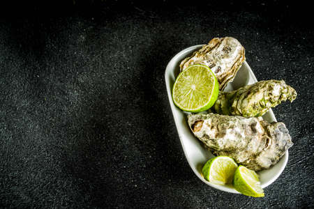 Fresh oyster clams with lemon on a black concrete background, top view copy space Stockfoto