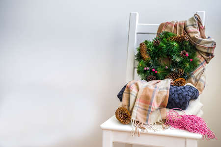 Christmas preparations, new year concept. Home decoration. Domestic interior, warm clothes sweater, plaid, scarf, Christmas tree wreath, with cones, berries. White wall, with chair, marshmallow cup Reklamní fotografie
