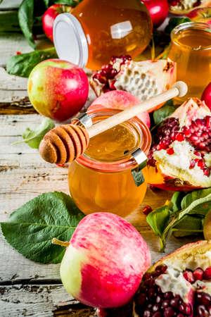 Jewish Autumn Rosh Hashana celebration. Traditional products for the celebration of Rosh Hashanah - apples with leaves, pomegranate, honey, honeycombs, white wooden  background Foto de archivo - 128246938