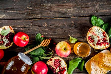 Jewish Autumn Rosh Hashana celebration. Traditional products for the celebration of Rosh Hashanah - apples with leaves, pomegranate, honey, honeycombs, wooden background Foto de archivo - 128246946