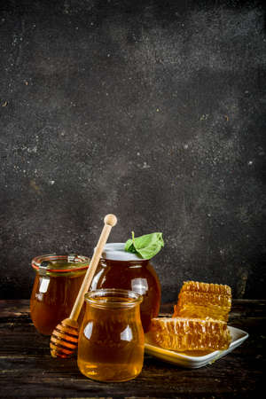 Autumn harvest. Organic farm honey in jars with honeycombs. Beekeeping products. On a wooden rustic background