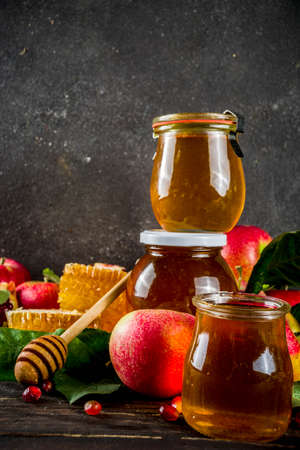 Jewish Autumn Rosh Hashana celebration. Traditional products for the celebration of Rosh Hashanah - apples with leaves, pomegranate, honey, honeycombs, wooden background Stock Photo