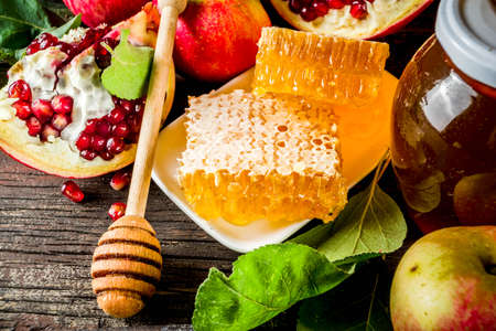 Jewish Autumn Rosh Hashana celebration. Traditional products for the celebration of Rosh Hashanah - apples with leaves, pomegranate, honey, honeycombs, wooden background Foto de archivo - 128246970