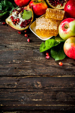 Jewish Autumn Rosh Hashana celebration. Traditional products for the celebration of Rosh Hashanah - apples with leaves, pomegranate, honey, honeycombs, wooden background Foto de archivo - 128246967