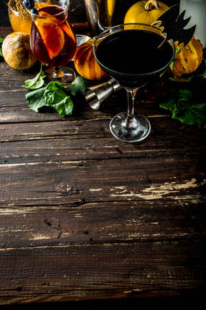Selection of Halloween traditional autumnal alcoholic cocktails and drinks. Different alcoholic beverages and shots for Halloween party, with autumn decorations, on a wooden table Stock Photo