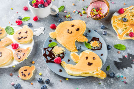 Halloween kids food treat. Funny pancakes - ghosts, jack o Lantern pumpkins, spider webs. Breakfast snack for childs Halloween party, with berries & candy,  gray stone table top view copy space Stock Photo