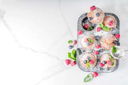 Homemade vanilla muffins or cupcakes with fresh berries on  white marble background Imagens