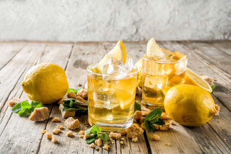 Lemonade or iced summer tea, with fresh lemon slices, sugar and mint leaf, rustic wooden table, copy space 写真素材