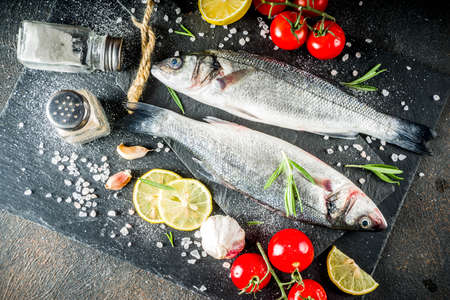 Raw sea bass fish with spices and ingredients, ready for cooking, dark concrete background copy space Stockfoto
