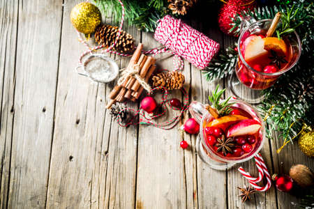 Traditional Christmas Mulled wine, grog or hot spicy sangria cocktail, on old rustic wooden table with christmas decorations and fir tree branches copy space top view