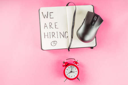 Creative top view flat lay  with we are hiring text on notepad with copy space, bright minimal style. With alarm clock. Concept of new job hiring recruitment process, screening of new team members. Stock Photo - 128588488