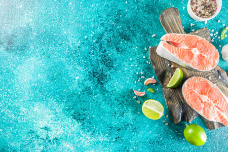 Raw salmon fish steaks with spices, on marine blue concrete stone background copy space