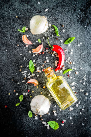 Cooking food stone concrete background with spices, olive oil, garlic, onion, pepper, herbs, basil. Top view copy space