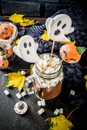 Funny idea for Halloween party, hot chocolate with decorative with marshmallows in shape of a ghost, pumpkin, monster, eyes,dark background copy space Banco de Imagens