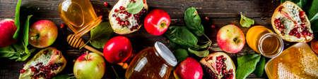 Jewish Autumn Rosh Hashana celebration. Traditional products for the celebration of Rosh Hashanah - apples with leaves, pomegranate, honey, honeycombs, wooden background banner 写真素材
