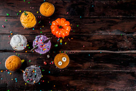 Funny childrens treats for Halloween: variations of cupcakes, decorated in the form of different monsters, witches, pumpkins, ghosts. Cooking process. On a wooden table, copy space for text, top view Banco de Imagens