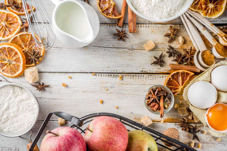 Autumn baking sale concept. Cooking seasonal fall baking background with ingredients, spices, apples, supplies, white wooden table top view copy space 写真素材