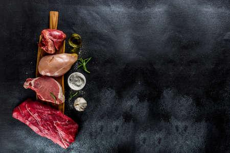 Vari tipi di carne. Carne di manzo rossa, bistecca di maiale, filetto di pollo, cuore di maiale di fegato, con spezie su sfondo di cemento di pietra nera vista dall'alto spazio copia