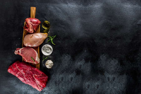 Various meat types. Red beef meat, pork steak, chicken filet, liver pork heart, with spices on black stone concrete background top view copy space