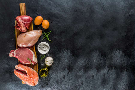 Various meat types. Red beef meat, pork steak, chicken breast filet, liver pork heart, with spices on black stone concrete background top view copy space Stock Photo
