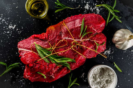 Raw beef tenderloin meat steak, with spices on a black cast iron skillet. Cooking food background.
