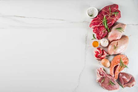 Carnivore diet background. Non vegan protein sources, Different meat food - chicken breast, pork steak, beef tenderloin, eggs, spices for cooking. White marble background copy space Foto de archivo - 128894348