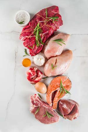 Carnivore diet background. Non vegan protein sources, Different meat food - chicken breast, pork steak, beef tenderloin, eggs, spices for cooking. White marble background copy space Foto de archivo - 128894359