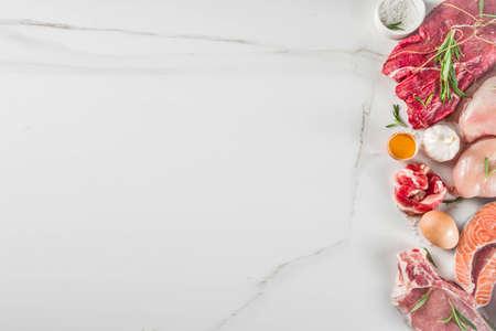 Carnivore diet background. Non vegan protein sources, Different meat food - chicken breast, pork steak, beef tenderloin, eggs, spices for cooking. White marble background copy space Foto de archivo - 128894380