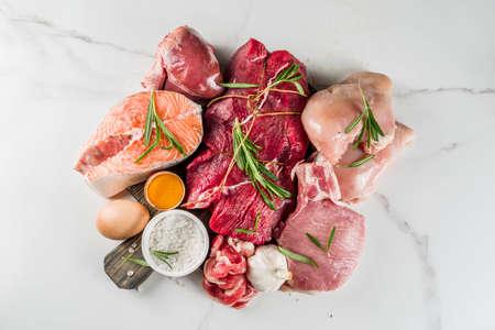 Carnivore diet background. Non vegan protein sources, Different meat food - chicken breast, pork steak, beef tenderloin, eggs, spices for cooking. White marble background copy space Foto de archivo - 128894387