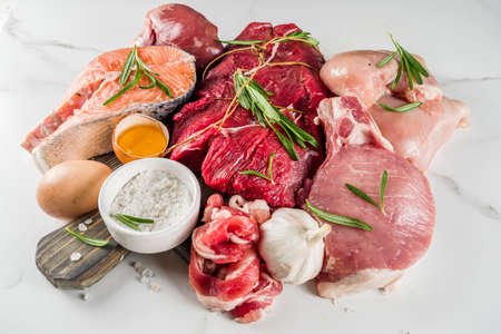 Carnivore diet background. Non vegan protein sources, Different meat food - chicken breast, pork steak, beef tenderloin, eggs, spices for cooking. White marble background copy space Foto de archivo - 128894384