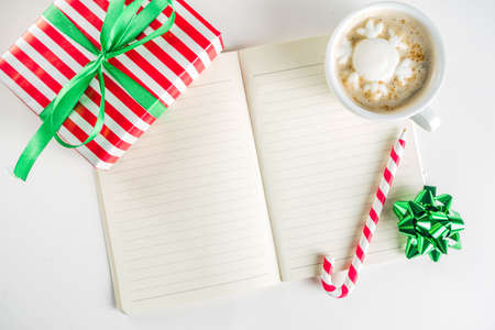 Preparation for Christmas background with gifts box, xmas decoration, coffee cappuccino cup and clear notepad for wishes, gift list or to do list. Top view flatlay copy space