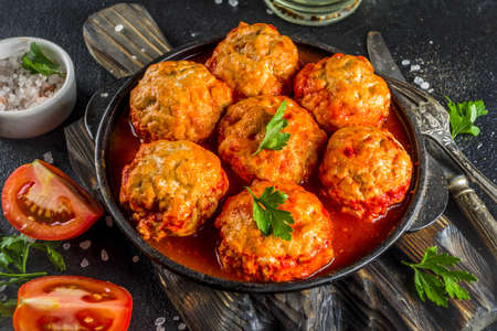 Homemade chicken meatballs in tomato sauce in a frying pan on dark stone or concrete table. Top view copy space Stockfoto