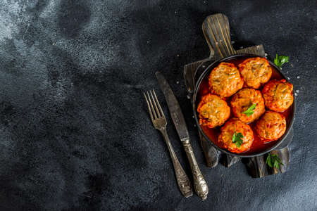 Homemade chicken meatballs in tomato sauce in a frying pan on dark stone or concrete table. Top view copy space Banco de Imagens